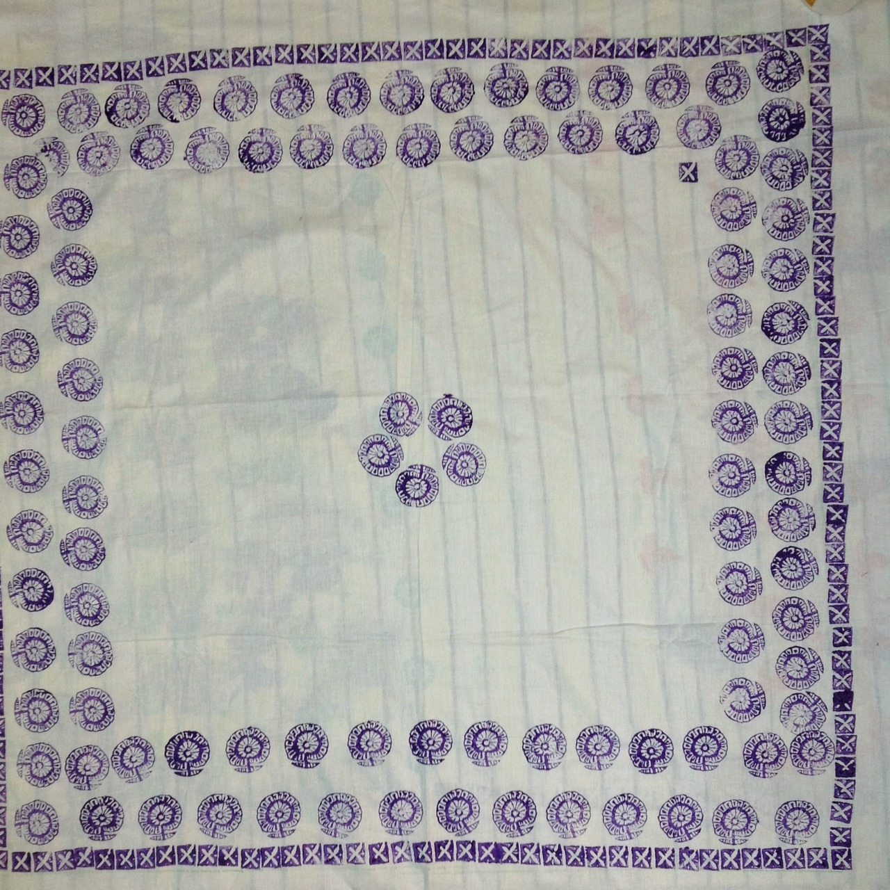 An unfinished hand block printed table cover in violet floral and geometrical print