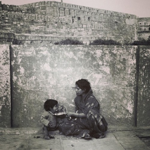 ammiephotographie:#mother feeding her #son in front of the red fort of #Agra #India #blackandwhite #blackandwhitephoto #blackandwhitephotography#streetbw