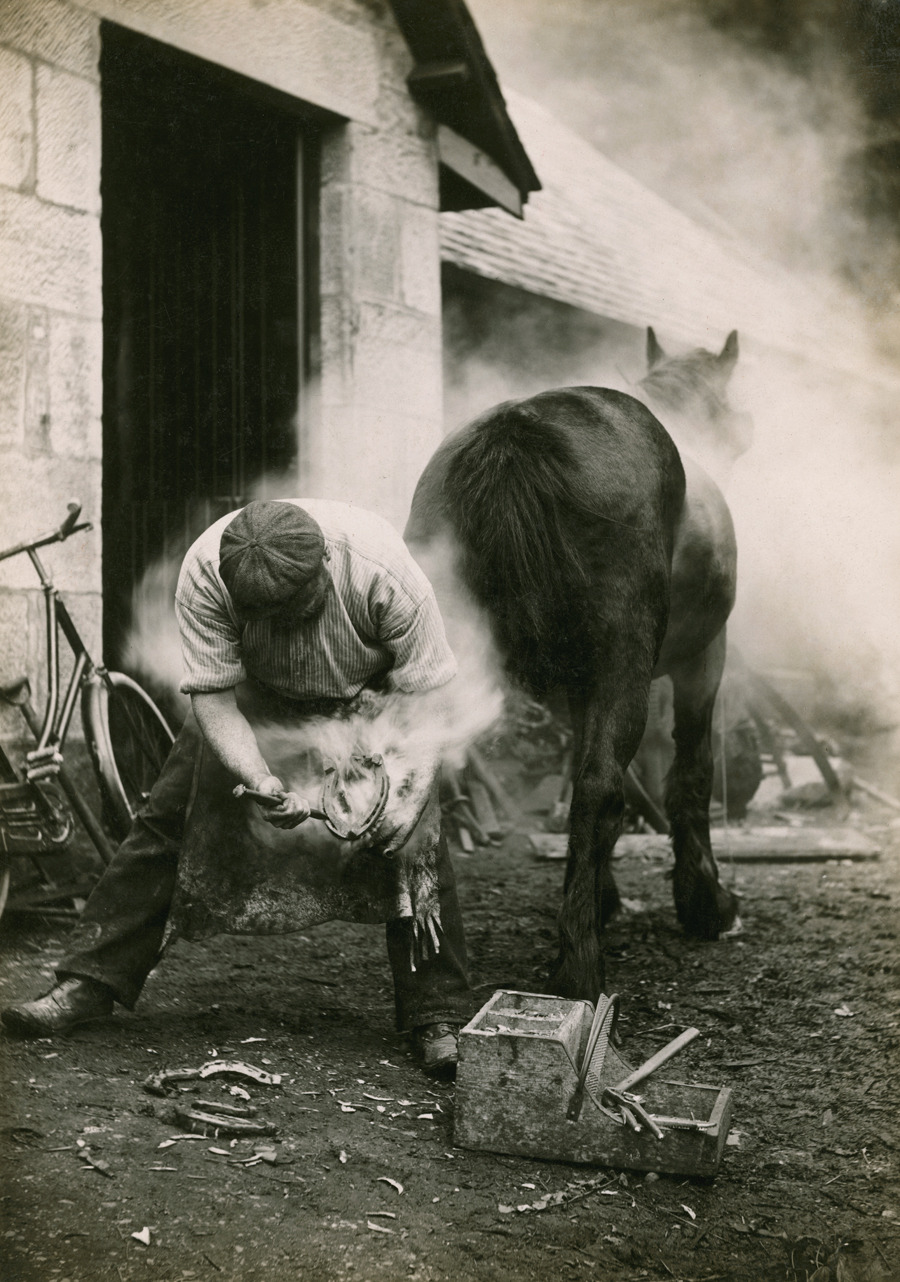 A farmer buring the hoof of a horse before shoeing it in Scotland, May 1921.Photograph by William Reid, National Geographic