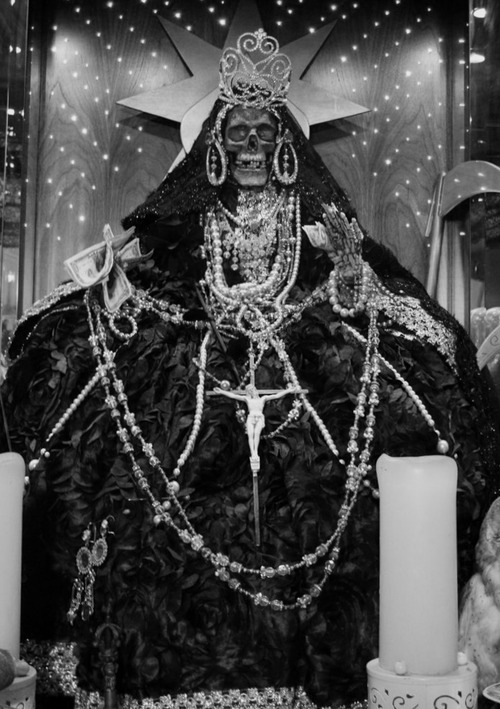 LA SANTA MUERTA<br /> The female grim reaper.<br /> The dark skeleton saint.<br /> She proudly sits on her throne<br /> with a crown tilted on her bony head.<br /> She loves her sacrifices.<br /> Sacrifices of humans—any humans.<br /> She will avenge your enemies<br /> and reward you with great wealth.<br /> Be evil and prosper.
