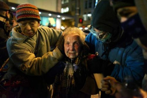 """carton-rouge:  84-year-old Occupy Seattle participant Dorli Rainey, pictured above after being pepper sprayed by Seattle Police on November 15th. She later wrote about the incident: """"Something funny happened on my way to a transportation meeting in Northgate. As I got off the bus at 3rd and Pine I heard helicopters above. Knowing that the problems of New York would certainly precipitate action by Occupy Seattle, I thought I better check it out. Especially since only yesterday the City Government made a grandiose gesture to protect free speech. Well free speech does have its limits as I found out as the cops shoved their bicycles into the crowd and simultaneously pepper sprayed the so captured protesters. If it had not been for my Hero (Iraq Vet Caleb) I would have been down on the ground and trampled. This is what democracy looks like. It certainly left an impression on the people who rode the No. 1 bus home with me. In the women's movement there were signs which said: """"Screw us and we multiply.'"""""""