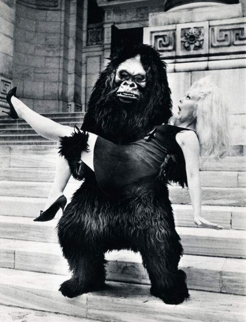 """Greta Thyssen does the blonde captive bit on the steps of New York's public Library with the help of a shaggy sidekick during the city's annual """"Salute to Fall""""….10-12-1967"""