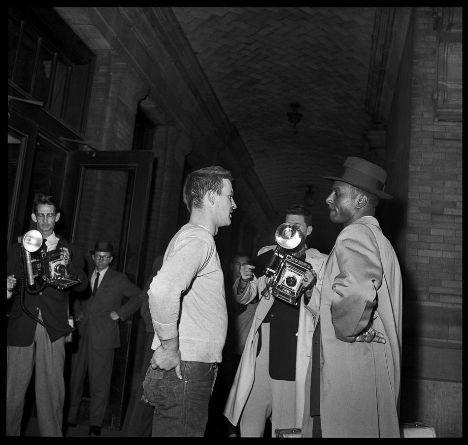 """The Rev. Fred Shuttlesworth, right, is stopped before entering the whites only waiting room at the Bus Terminal March 6, 1957, in Birmingham, Ala. This photo was made one day after the Alabama Public Service Commission ruled that the waiting rooms must remain segregated. Shuttlesworth informed the media of his plans to integrate the waiting rooms and was followed by reporters, photographers and a white mob estimated at more than 100. After being told that he was not wanted inside, Shuttlesworth replied: """"It's not up to you to tell me where to go."""" ( AP Photo/The Birmingham News, Robert Adams)"""