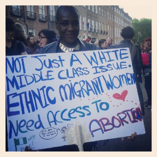 "Woman holding a sign saying ""Not just a white middle class issue: ethnic migrant women need access to abortion."""