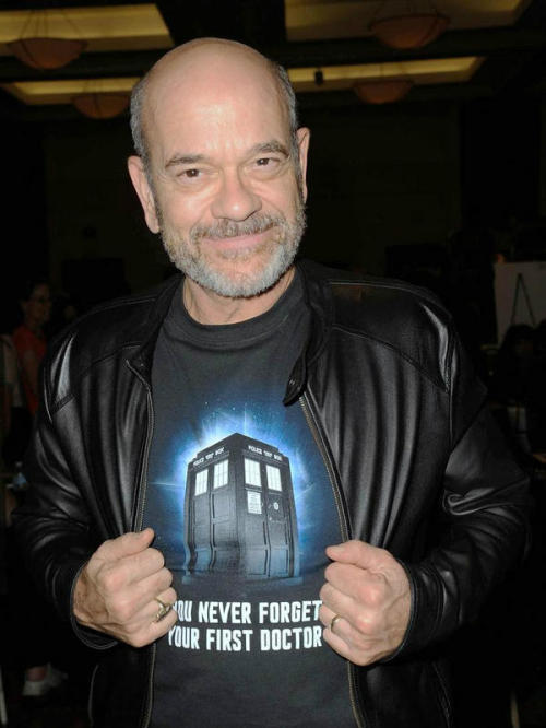 Actor Robert Picardo (who played the holo-doctor on Star Trek Voyager) opens his leather jacket to display his Doctor Who t-shirt showing the TARDIS and captioned YOU NEVER FORGET YOUR FIRST DOCTOR