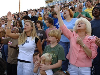 A large group of Evangelical Christians, gathered at a football stadium, raise their arms and hands to God--they swoon.