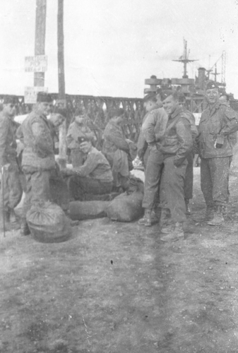 250. 7 August 1945, waiting dockside to board the ship in background on the way to England. It is all over.