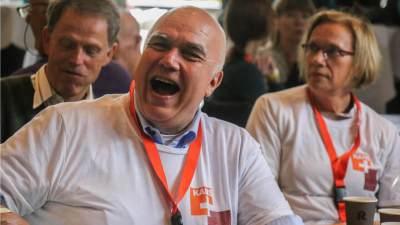 Een lachende man in de zaal tijdens het jubileumfeest