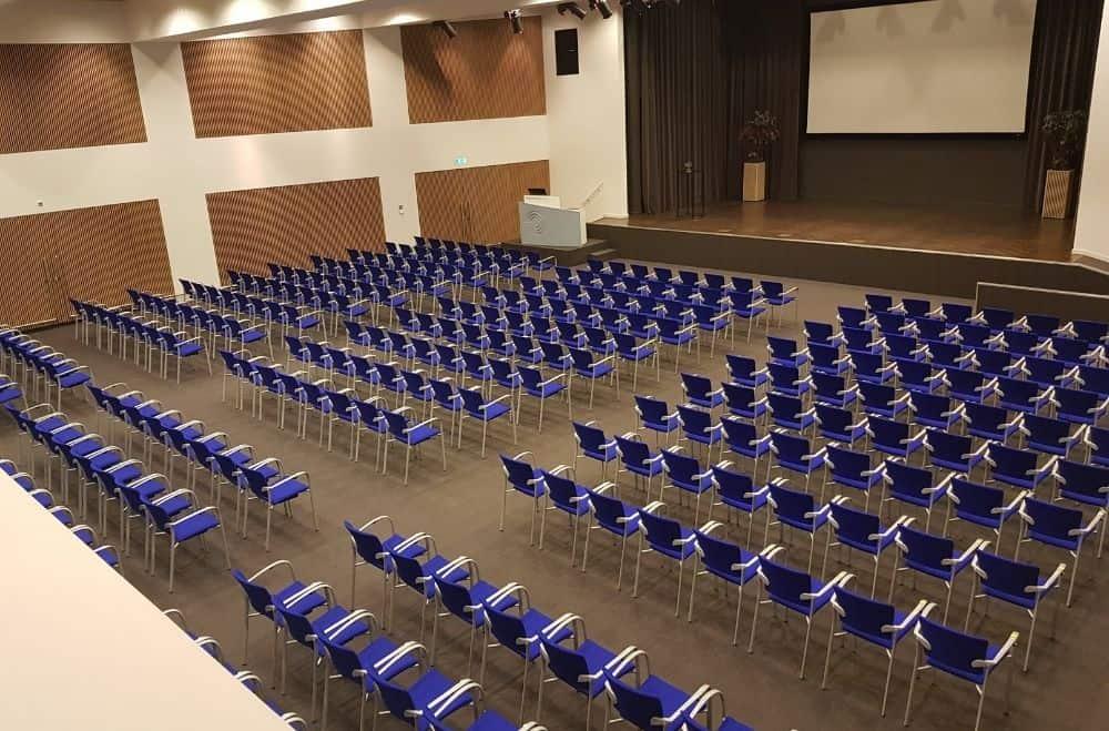Een congres of zakelijke bijeenkomst tijdens corona organiseren. een congres zaal met lege stoelen