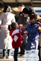 A refugee mother gives treats to her kids Munich citizens handed to her.
