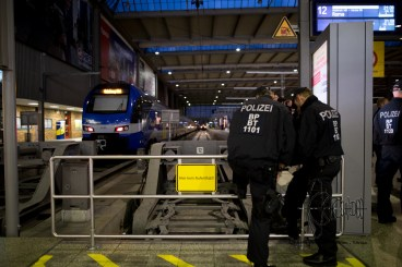 """Policemen awaiting the next train from Italy next to a sign saying: """"No stay"""""""