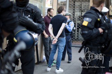A young man gets handcuffed for not showing his ID immediatly walking around the German unity party mile.