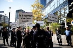 Protestors show their mischief of German asylum politics with ironic signs.