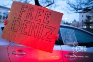 Participants hold up signs asking for Deniz' release.