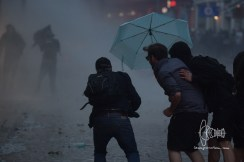 Man standing in umbrella charching water cannon