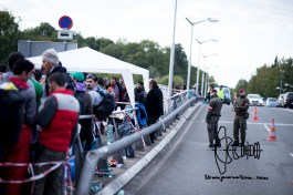 Refugees await in line to cross over the river to Germany.