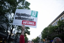 """Members of the left party """"Die Linke"""" holding up a sign """"Refugees welcome!"""""""
