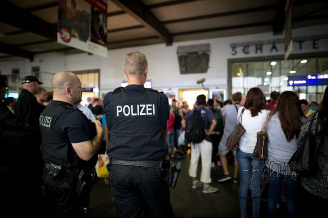 Policemen watching refugees line up for registration process.