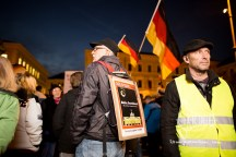 """Man with """"Der Spiegel"""" cover page stands amongst the PEGIDA crowd."""