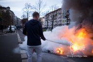 A resident uses fire extinguisher to stop barricades from burning.