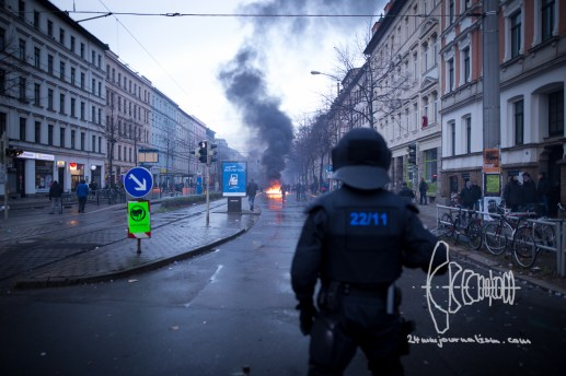 Riot police forces watch burning barricades.