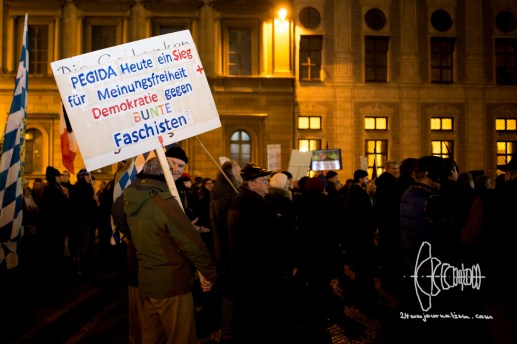 PEGIDA gathers. A man carries a sign entiteling counter-protestors as facists.