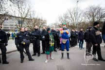 Clowns posing in front of riot police officers.