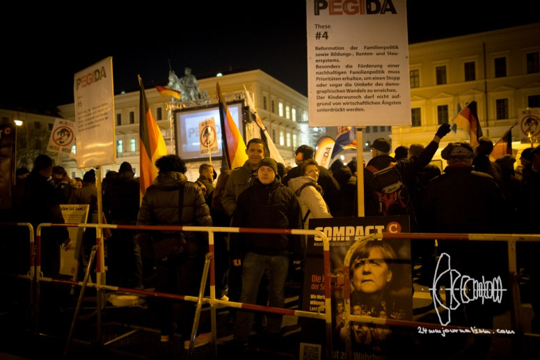 "Neo-nazis watch counter protest as PEGIDA returned to starting point. Karl Heinz Statzberger wears beanie of neo-nazi party ""III. Weg"""