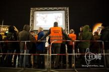 """2017-03-07 PEGIDA München Teilnehmer mit Weste mit der Aufschrift """"Abschiebehelfer. PEGIDA München am Karlsplatz, Stachus. Etwa 40 Personen beteiligen sich an der Kundgebung des Münchner PEGIDA Ablegers. 13 Gegendemonstranten werden verhaftet, nachdem sie auf eine Gruppe Neonazis mit Transparent zudrängten. In unmittelbarer Nähe zur Kundgebung wird ein HAkenkreut frisch gesprüht."""