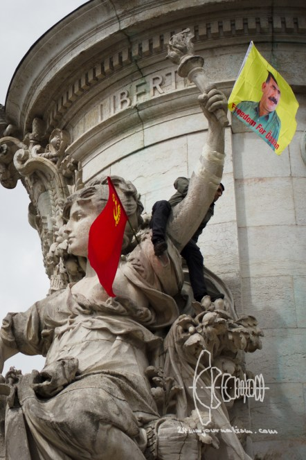 """A protestor clims on a statue and attaches a """"Freedom for Öcalan"""" flag below the words """"Liberty"""""""