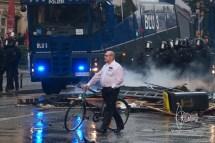 Man walking through riot with his bike