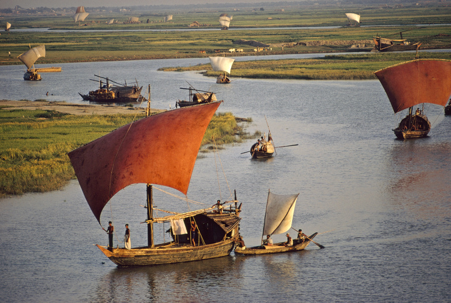 Red sailed wood sailboats travel the winding Turag River in Bangladesh, September 1972.Photograph by Dick Durrance II, National Geographic