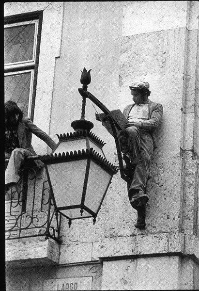 This guy reads.cafeparaacordarosmortos:Homem lê o jornal, sentado num candeeiro público, enquanto uma revolução acontece debaixo dele.Lisboa, 25 de Abril de 1974 Carlos Gil