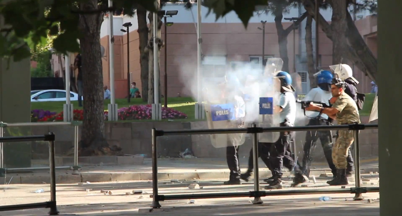 In this photo, a member of the armed forces standing alongside the police fires teargas at people (location unconfirmed)