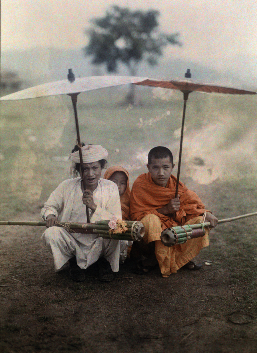 Shan man and two priests prepare to set off bamboo rockets in rain, Myanmar, November 1931.Photograph by W. Robert Moore, National Geographic