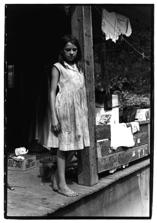 William GedneyYoung girl standing on a porch leaning against a support beamKentucky, 1964[via the Duke University Libraries]