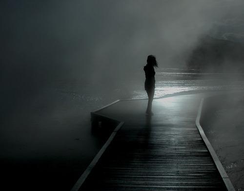Mulher num cais em meio à neblina