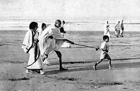 Gandhi conduzido por um garoto. Na praia, claro.