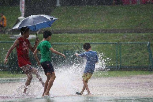 image of children out playing in the street during rain
