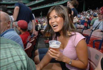 """This woman is watching a sporting event of some kind. IS THIS FEMINIST?  No. The culture of sports is a sort of miniaturized warfare, which incites the individual to lose him- or herself in identification with his or her """"team,"""" in a proto-nationalist fashion, making him or her complicit in an exercise of brutal, organized physical domination of the enemy """"team."""" Thus, sporting events create and support a patriarchal conception of """"power-over"""" in which victory — and thus worth — is defined by physical domination and conquest of the Other. It's still feminist to watch """"Friday Night Lights,"""" though. PROBLEMATIC."""