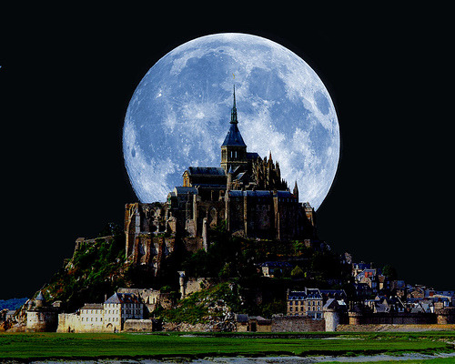 a small castle in the dark with a big blue moon right behind it
