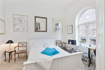 white bedroom with a blue pillow