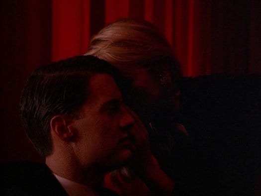 Laura Palmer leans in to whisper something to Dale Cooper. Her face is covered by his profile.