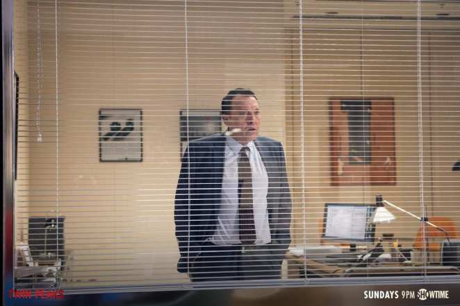 Anthony Sinclair looks through his office blinds and panics