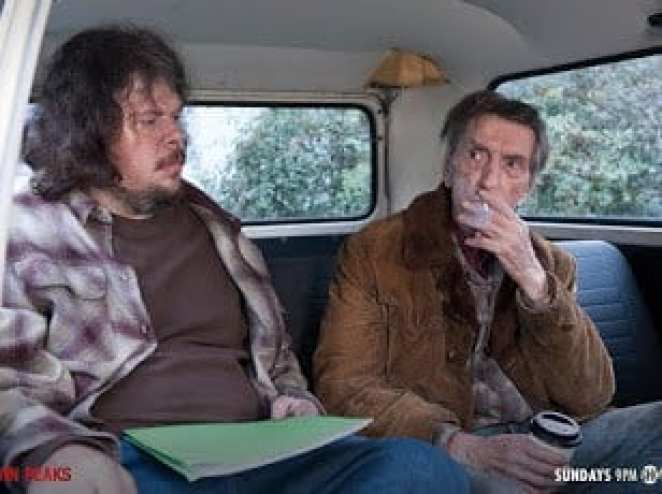 Carl Rodd smokes a cigarette with Mickey in a van
