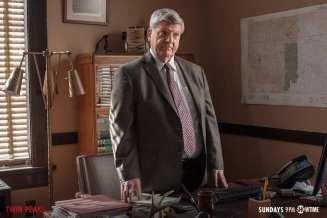 detective mackley stands at his desk