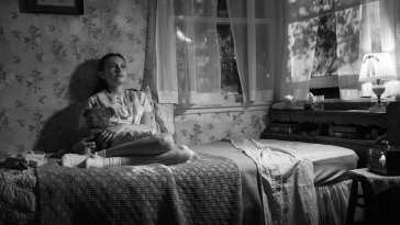 girl with teddy sits on her bed at night thinking