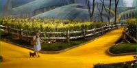 Dorothy and Toto walking down the yellow brick road, approaching a crossroads in the path.