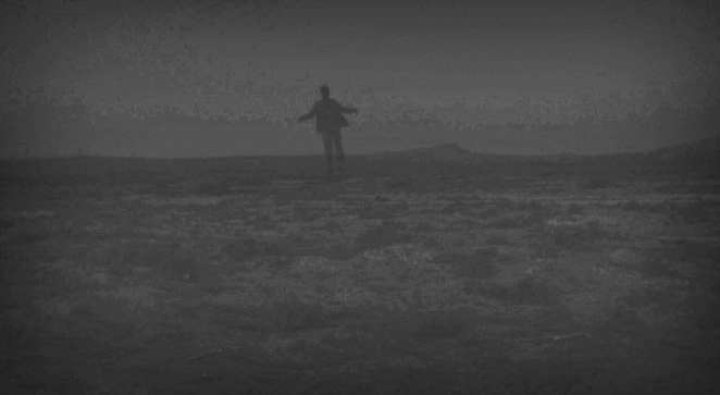 Woodsman floating to the ground in the desert at night