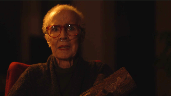 The Log Lady with breathing tubes in her nose holds her log